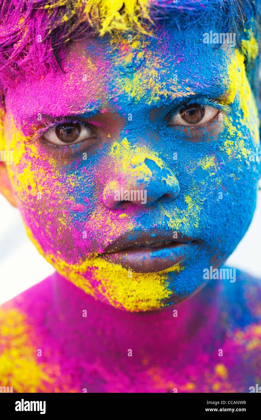 Giovane ragazzo indiano coperto di polvere colorata pigmento. India Immagini Stock