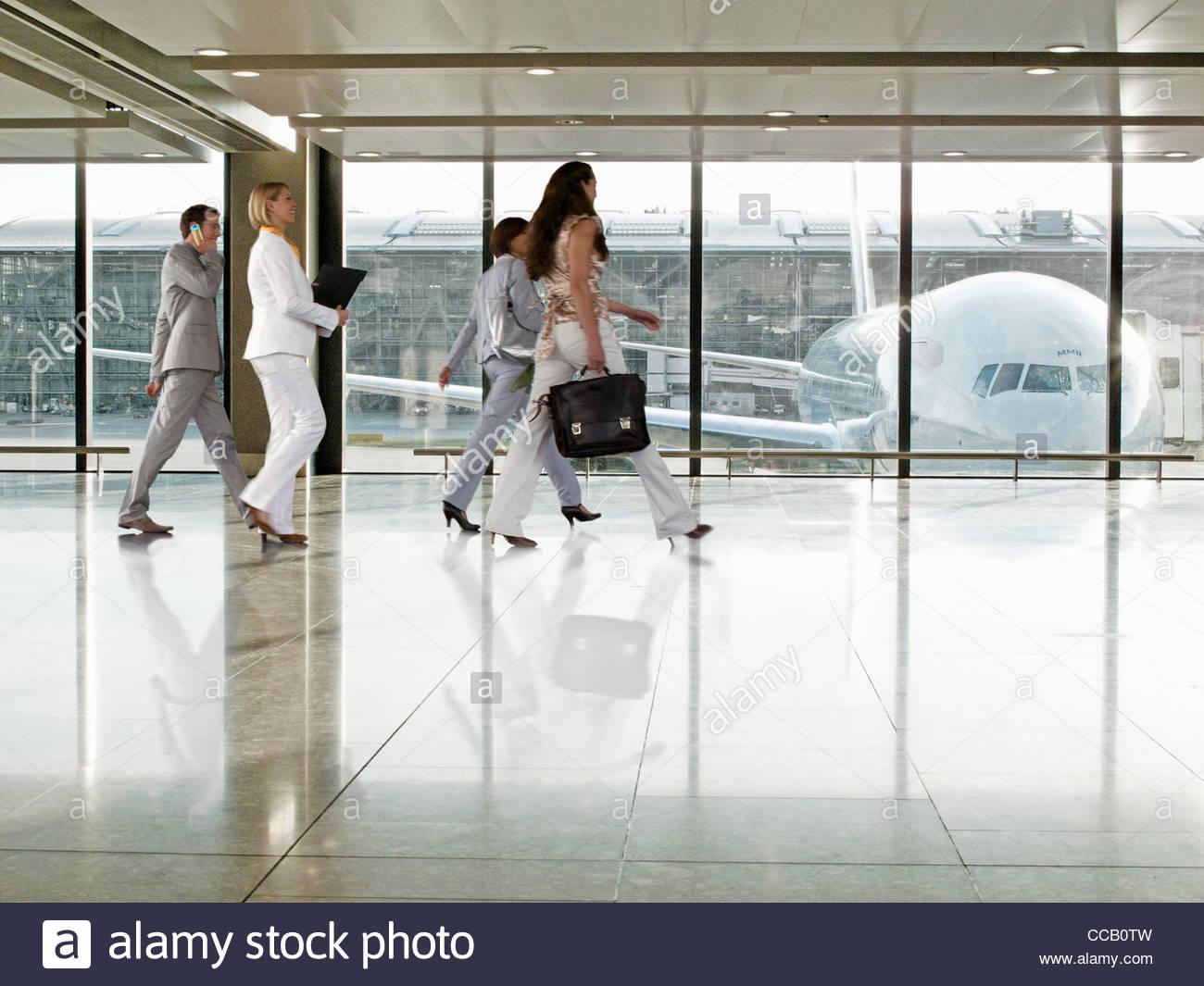 La gente di affari a piedi nel terminal dell'aeroporto Immagini Stock