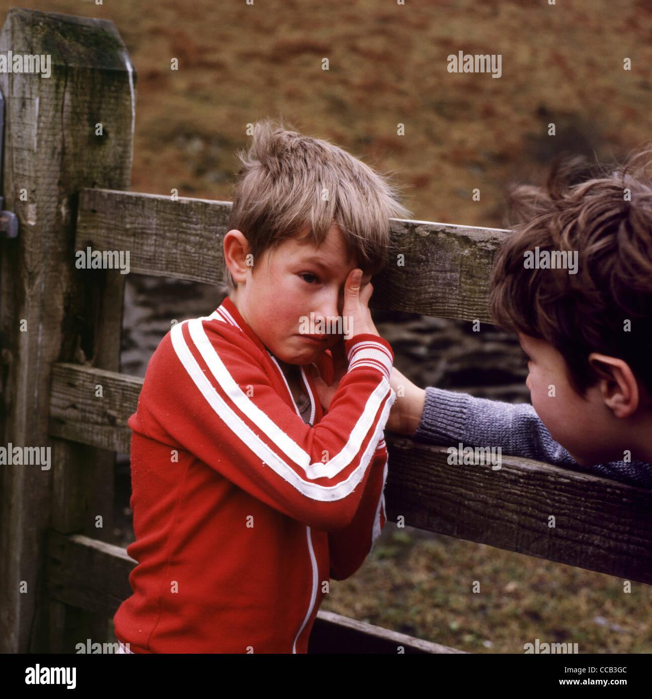 Scuola ragazzo in lacrime essendo mostrato compassione ed empatia e confortato da un amico da un cancello in legno Immagini Stock