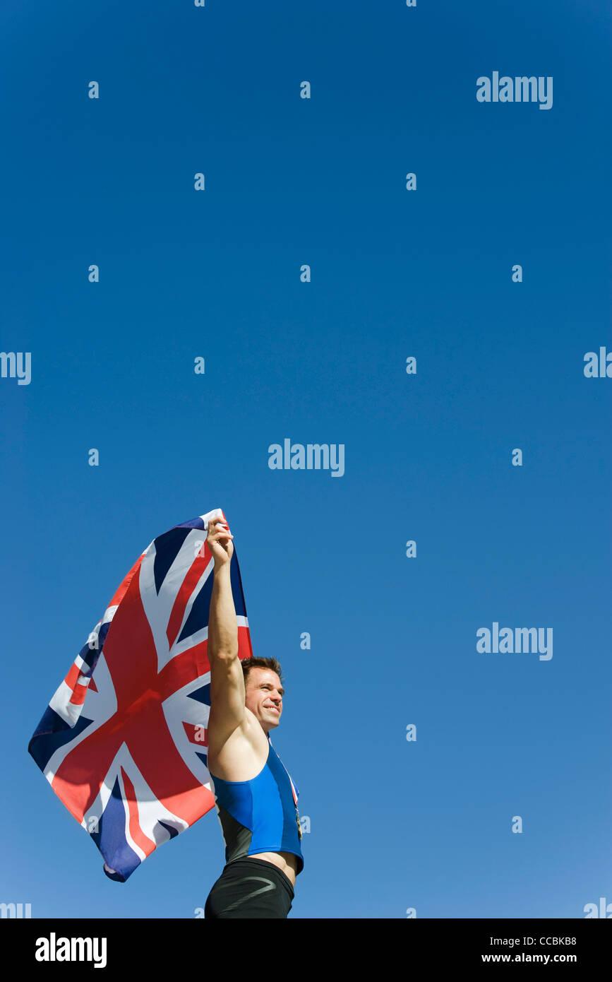 Atleta maschio mantenendo la bandiera britannica Immagini Stock