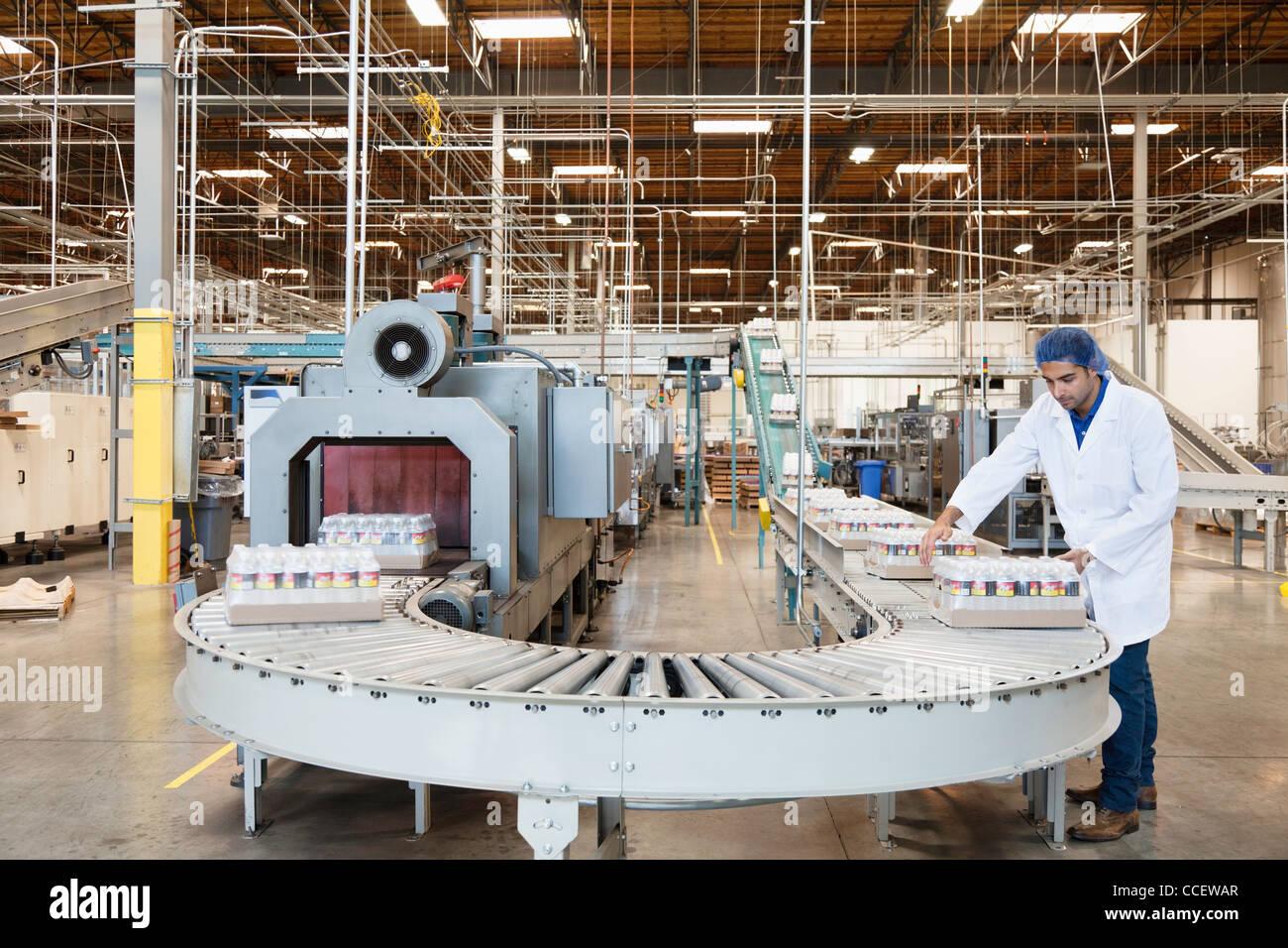 Uomo che lavora nella fabbrica di imbottigliamento Immagini Stock