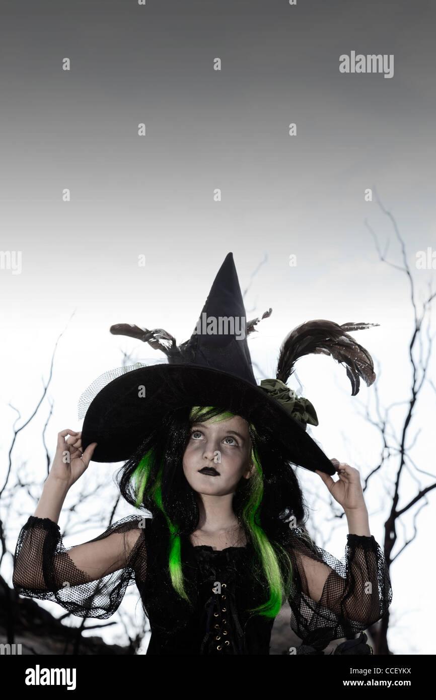 Ragazza costume come strega guardando verso l'alto tenendo il suo cappello Immagini Stock