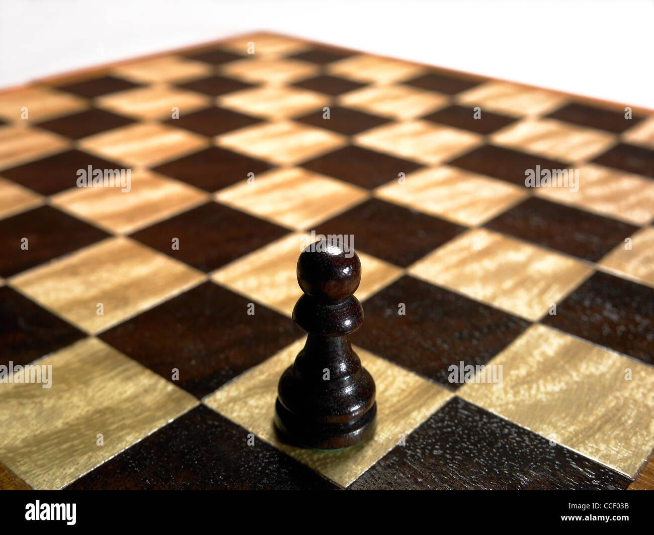 Una pedina pezzo degli scacchi su una scacchiera vuota Immagini Stock