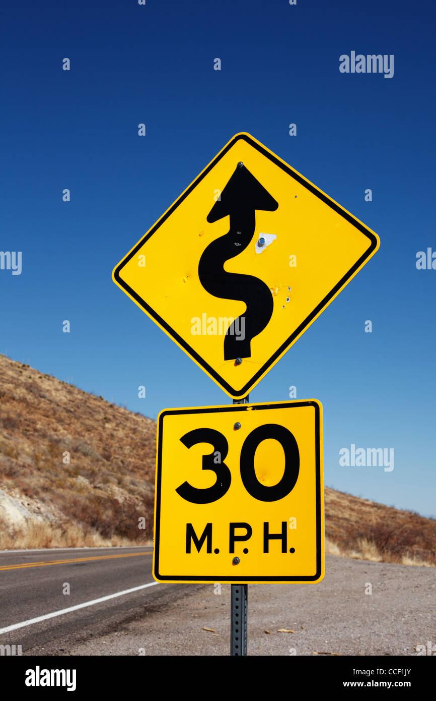 Una autostrada segno indicante le curve davanti. Immagini Stock