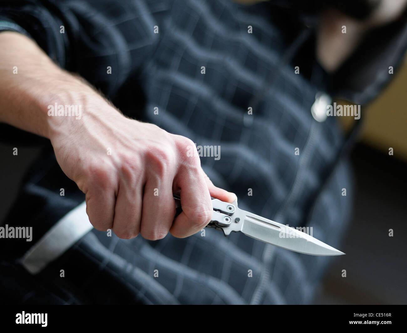 Il crimine di coltello. Maschio con cappuccio brandendo un coltello butterfly. Immagini Stock