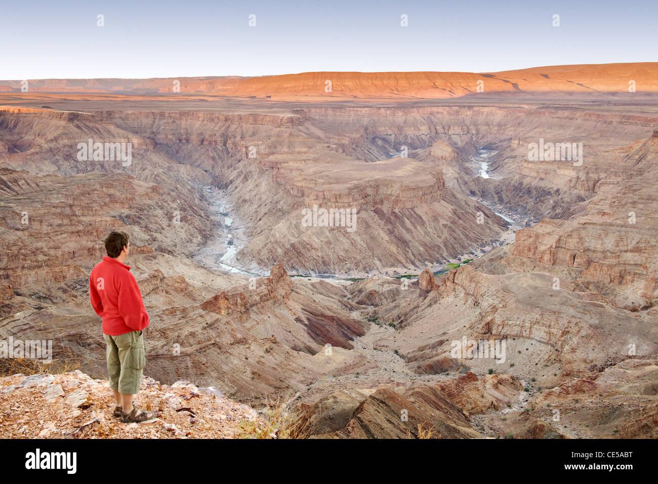 Un uomo sta guardando fuori attraverso il Fish River Canyon nel sud della Namibia all'alba. Immagini Stock
