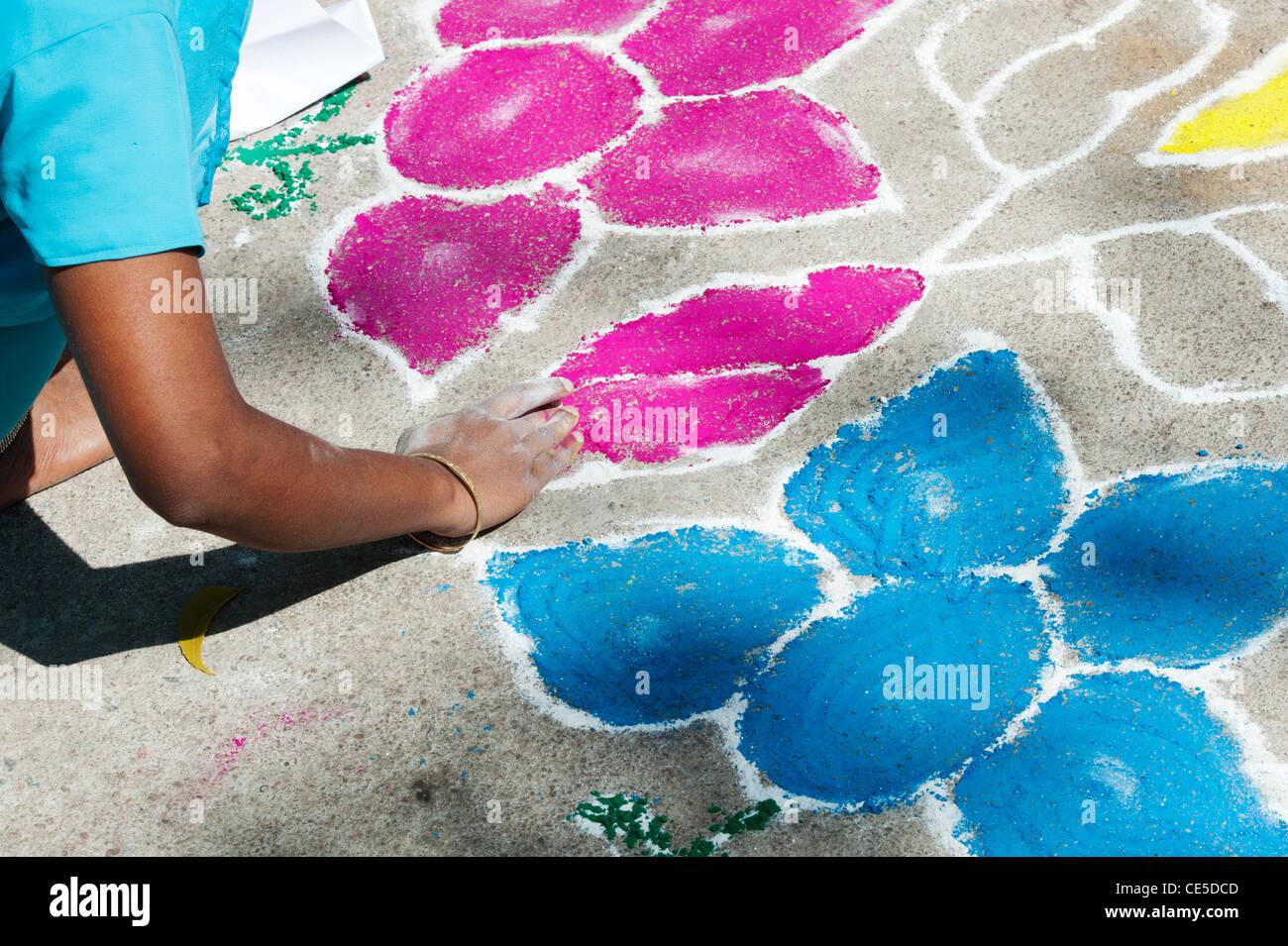 India donna fare un festival Rangoli di polvere colorata design in un Indiano street. Puttaparthi, Andhra Pradesh, Immagini Stock