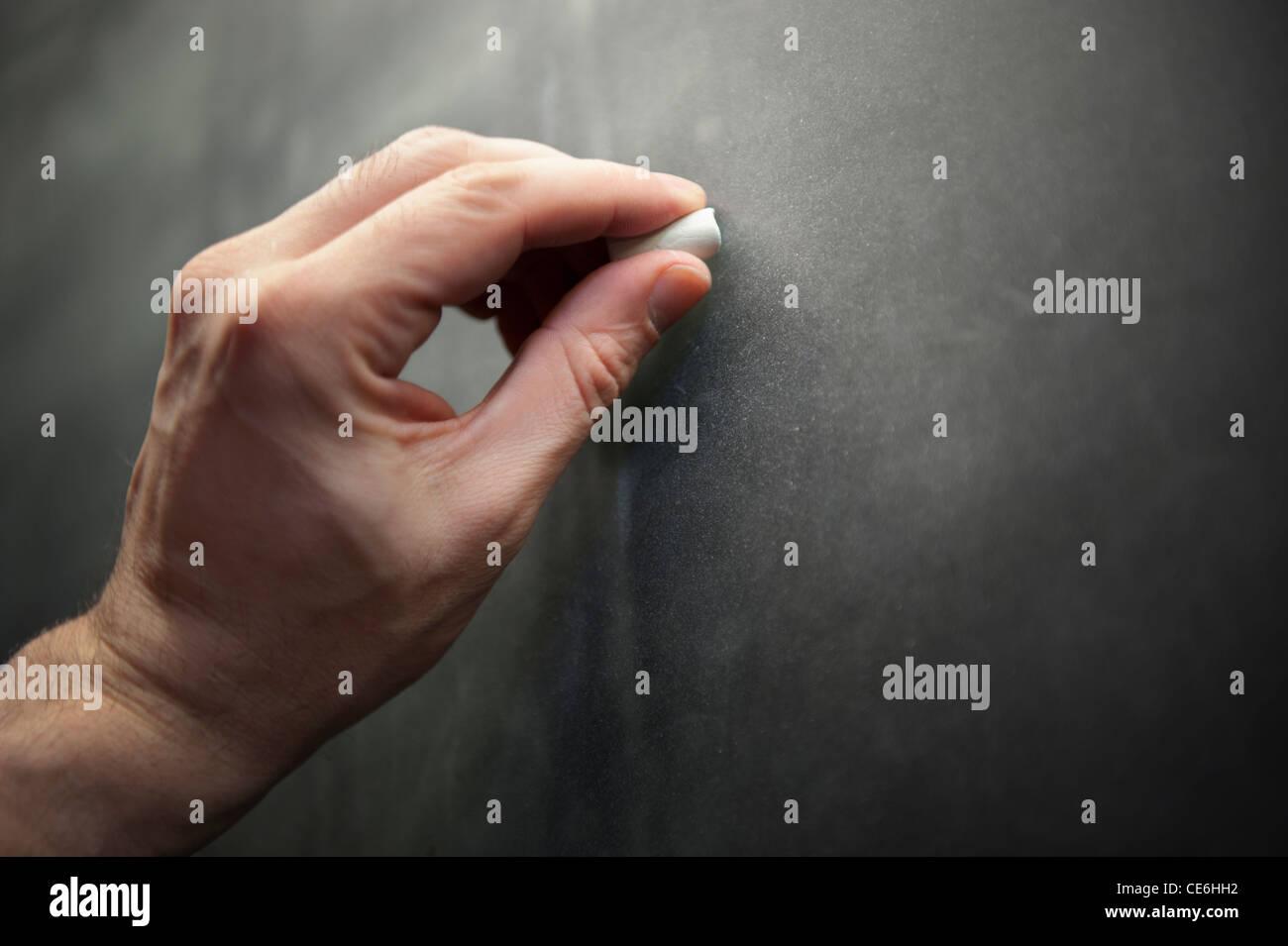 Un uomo insegnante maschio lato sinistro scrive usando il gesso su una lavagna Lavagna. Immagini Stock