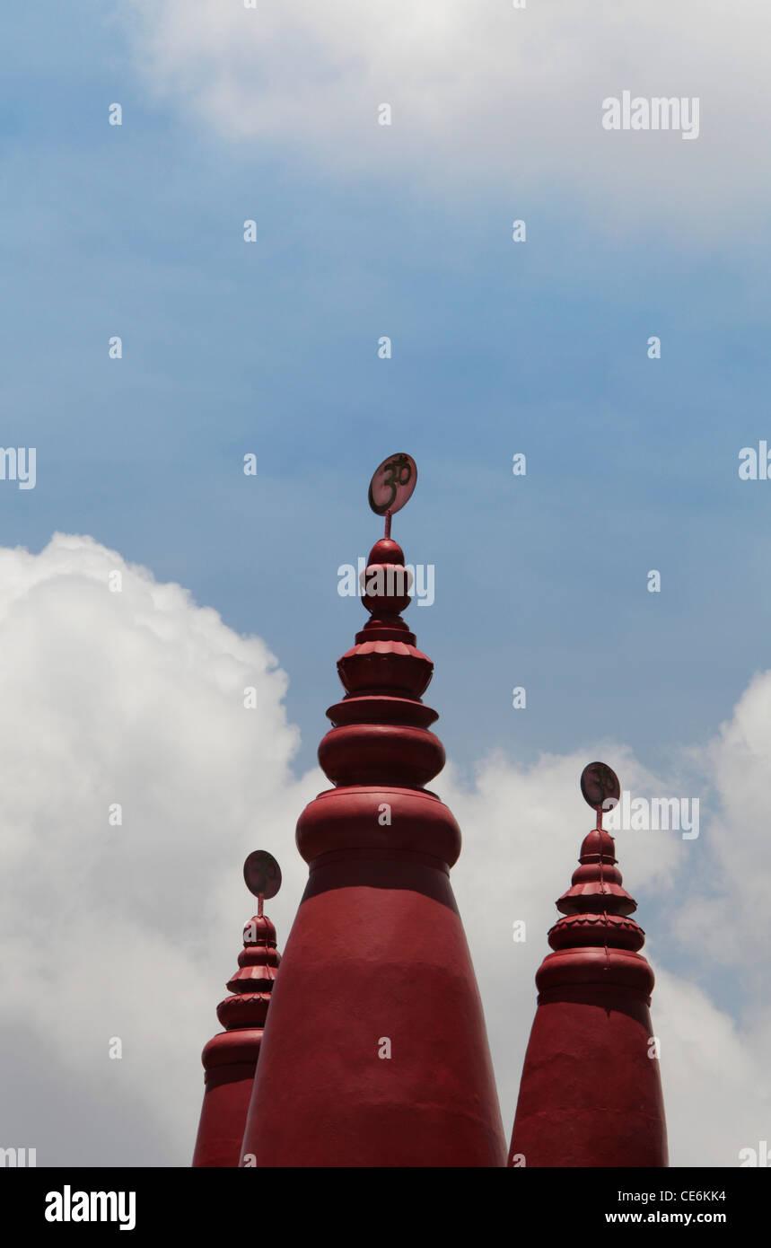 Red le torrette del tempio indù con OM in sanscrito sulla parte superiore. Immagini Stock