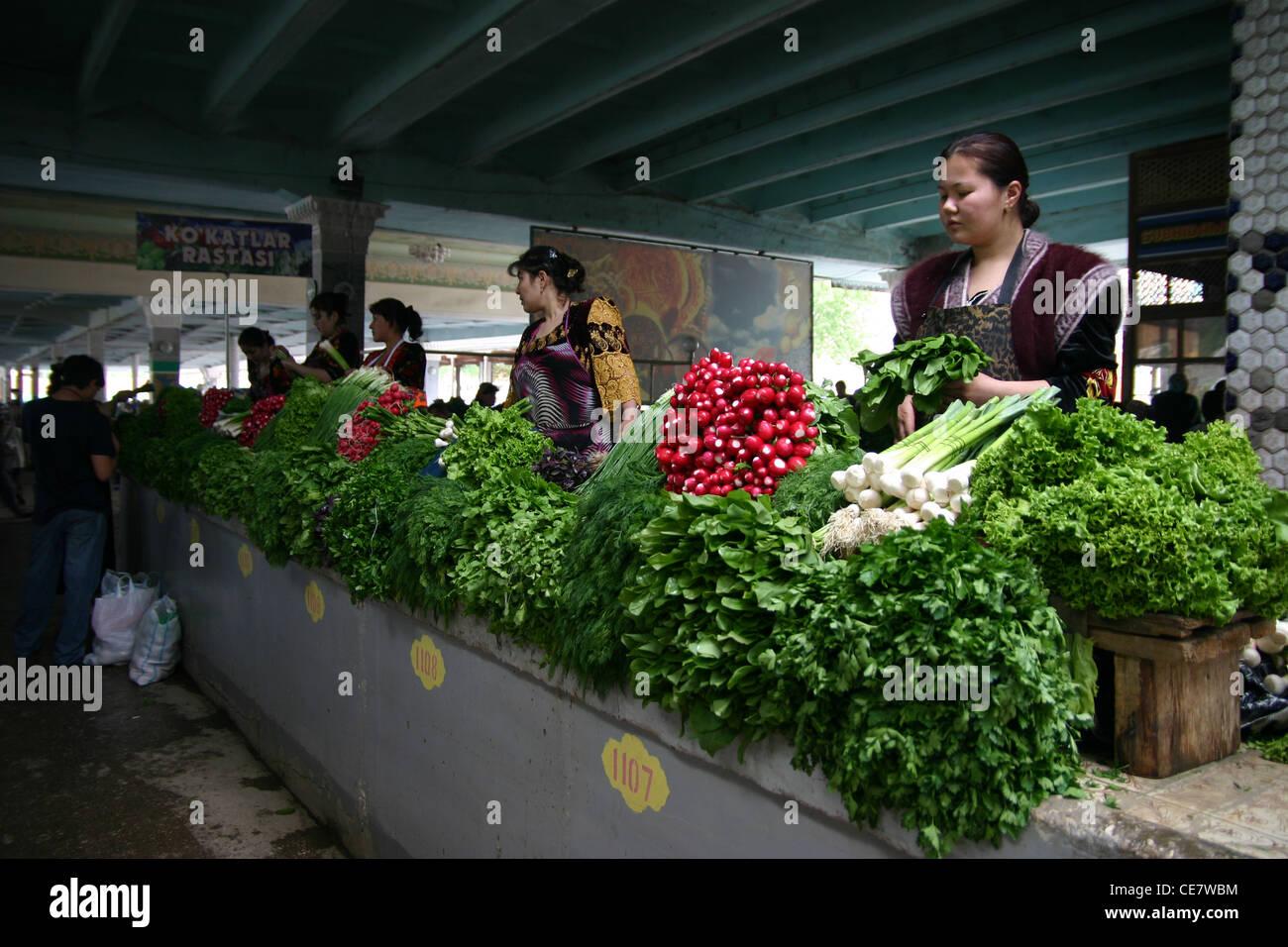 Signora tradizionali verdure di vendita in un mercato di Samarcanda in Uzbekistan Immagini Stock