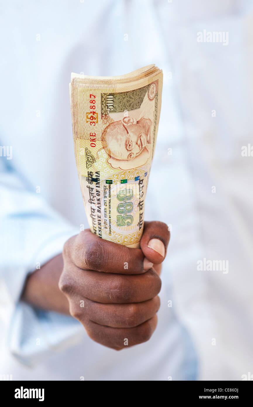 Indian man mano che tiene un mazzetto di 500 rupee note che sono state demonetised nel novembre 2016. India Immagini Stock