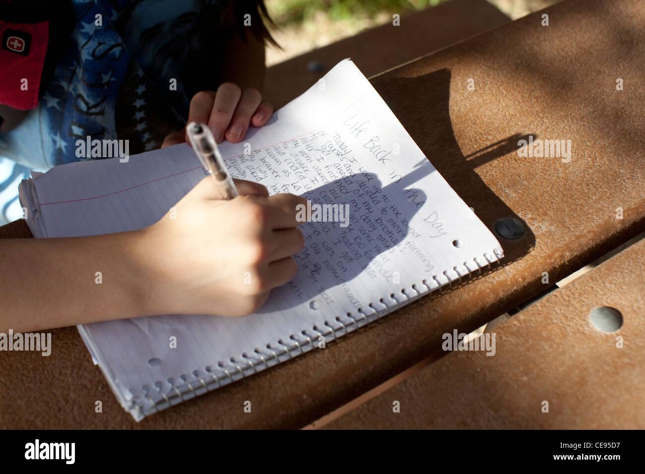 Teenage middle school studentessa scrive a mano relazione scuola durante il viaggio di campeggio al parco nazionale Immagini Stock