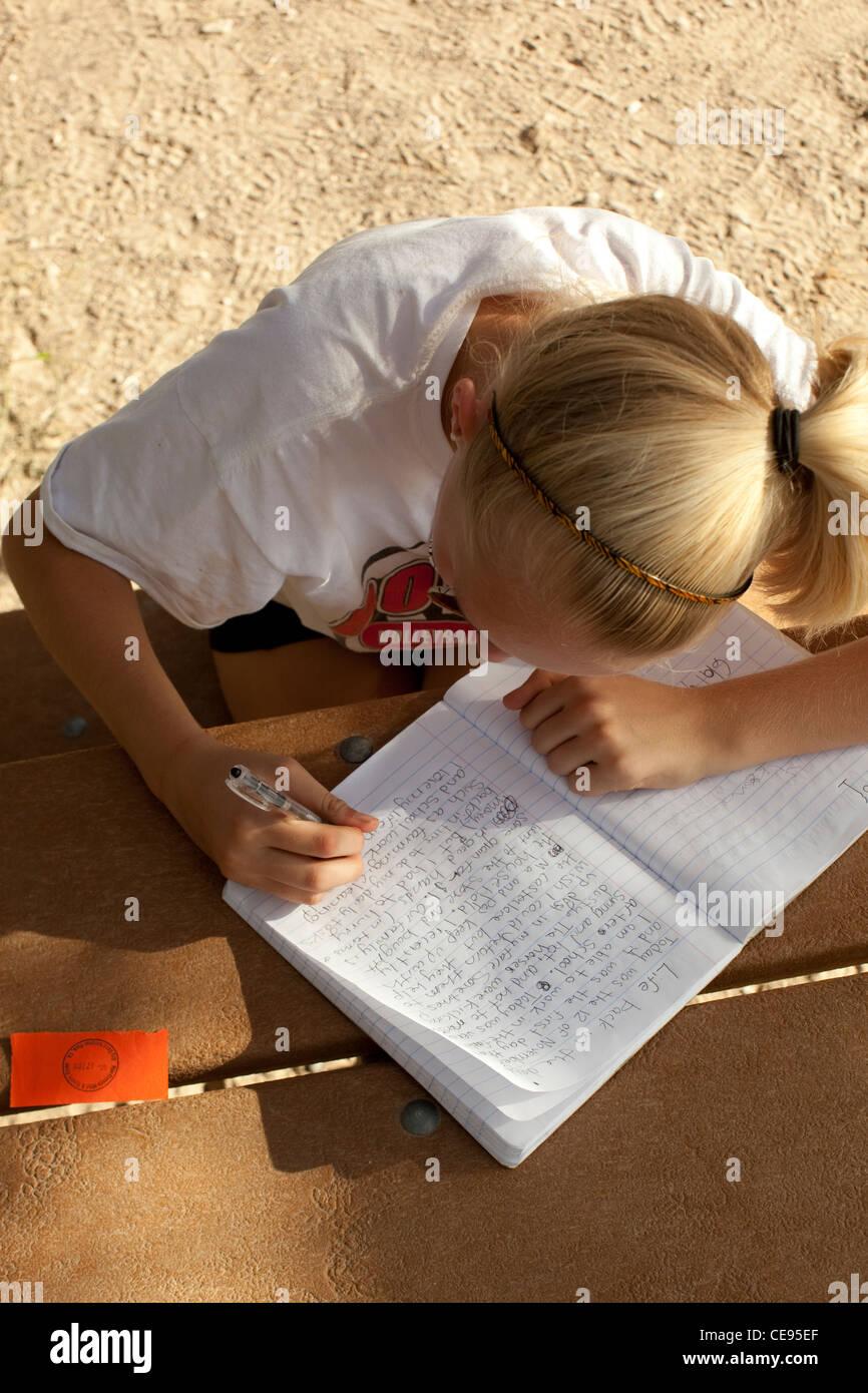 Teenage gli studenti delle scuole medie scrive a mano relazione scuola durante il viaggio di campeggio al parco Immagini Stock
