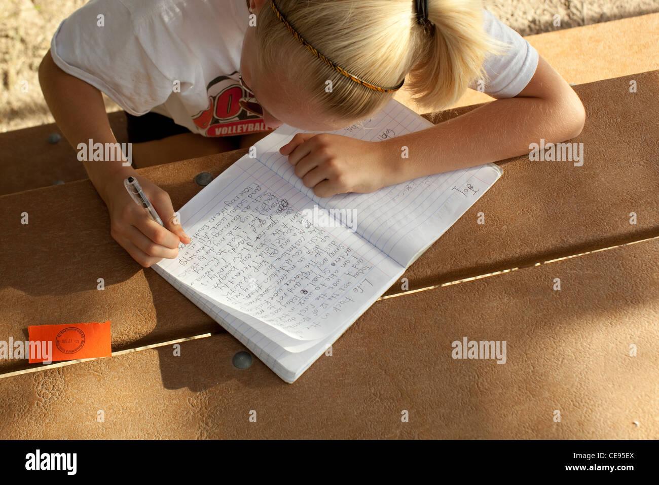 Centro Adolescenti scuola studente scrive a mano relazione scuola durante il viaggio di campeggio al parco nazionale Immagini Stock