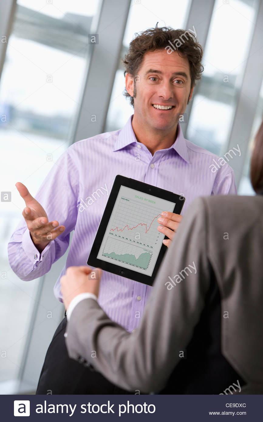 Imprenditore imprenditrice che mostra il grafico su tavoletta digitale Immagini Stock