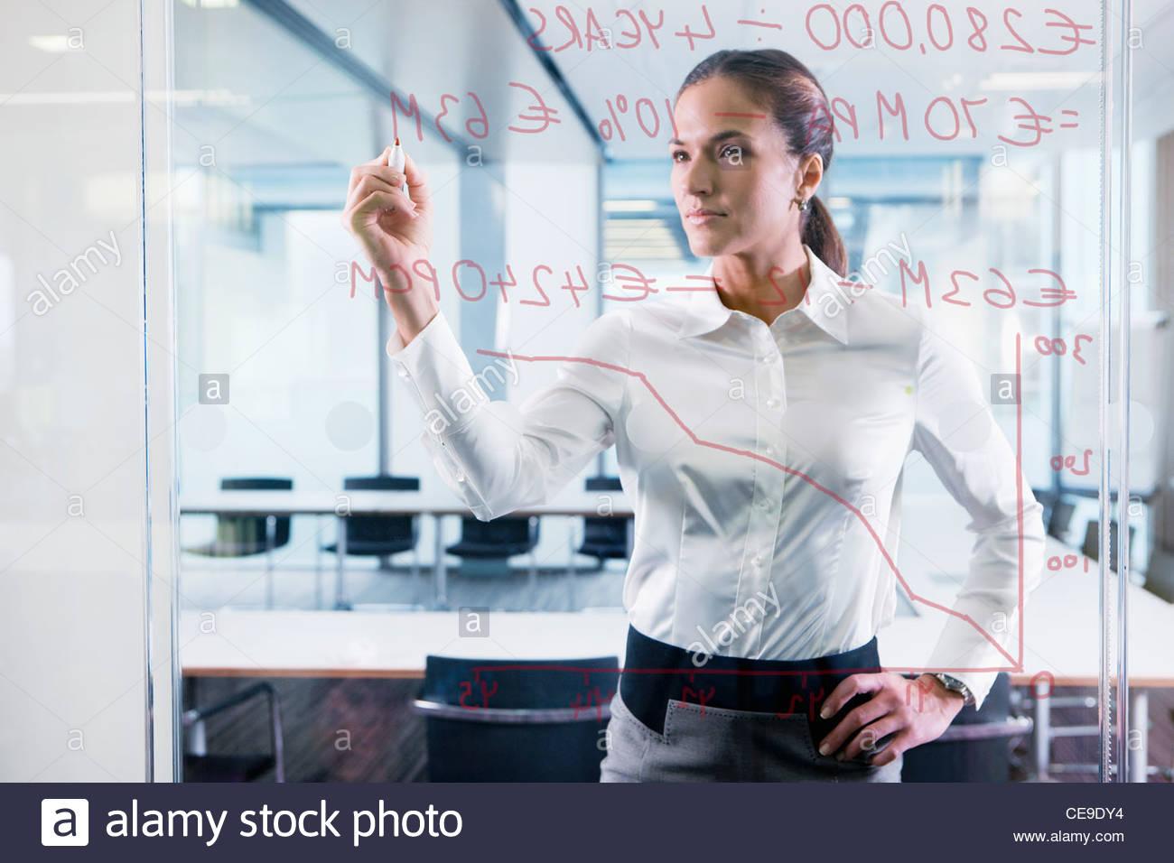 Imprenditrice disegno grafico sulla finestra in vetro in office Immagini Stock