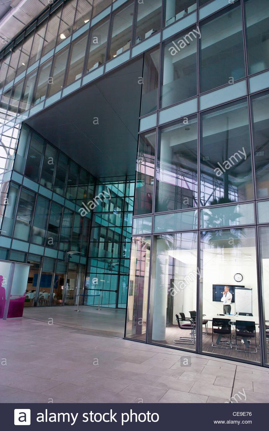 Vista del pensieroso imprenditore in piedi nella sala di conferenza highrise building Immagini Stock