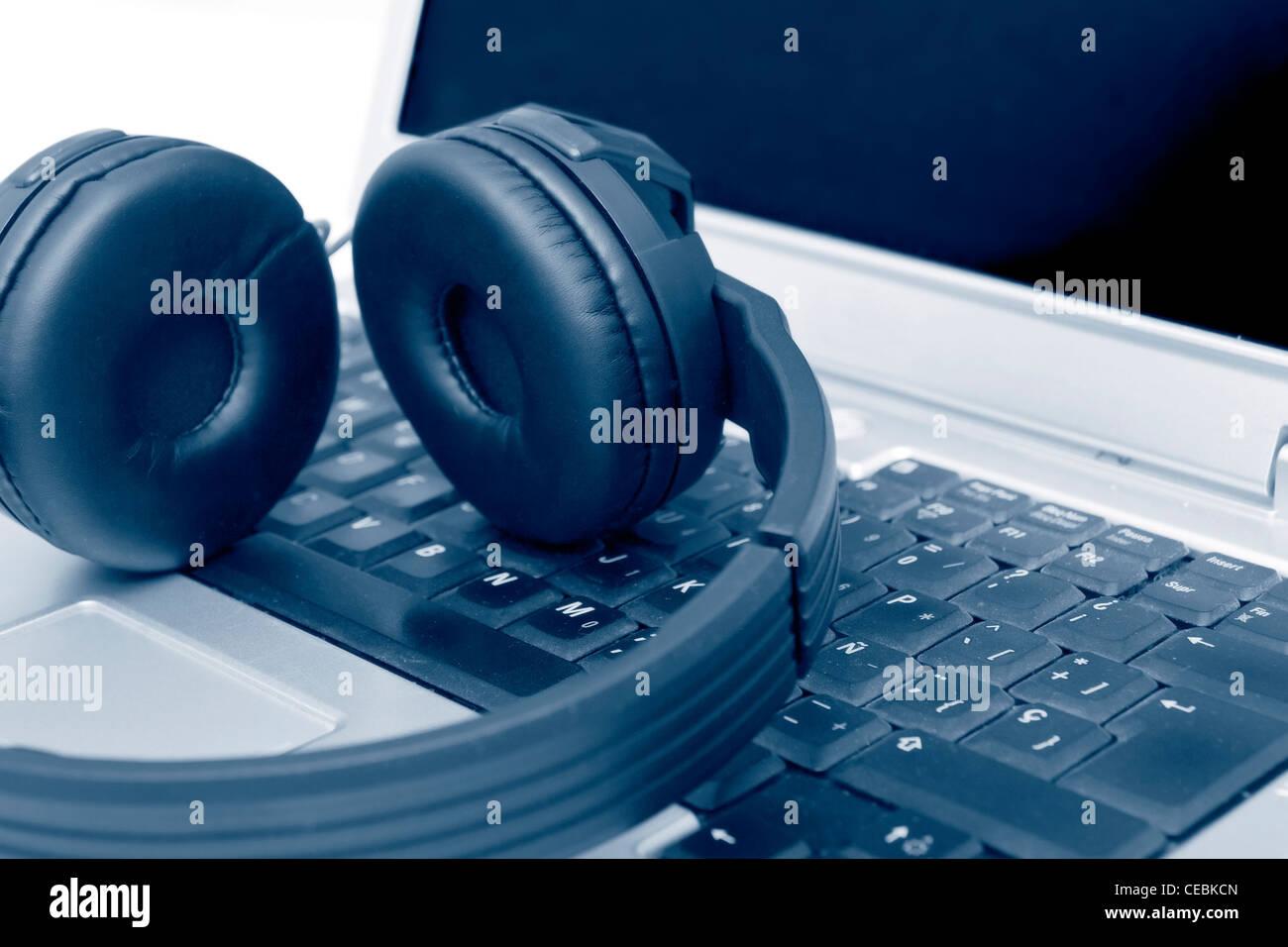 Cuffie sul computer portatile Immagini Stock