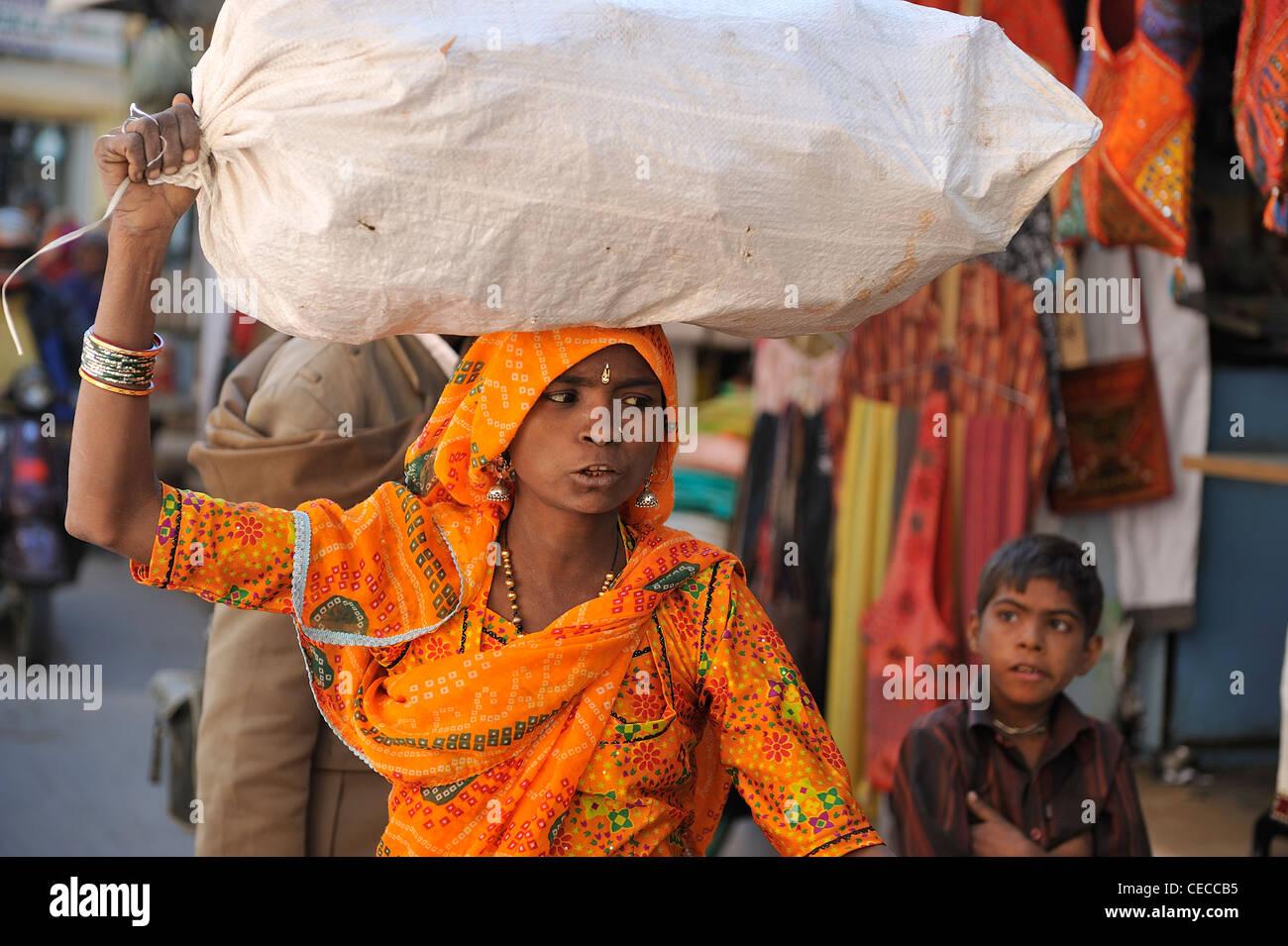 Donna in India sono per il duro lavoro e la vita di portare carichi pesanti sulle loro teste come qui in Jaisalmer; Immagini Stock