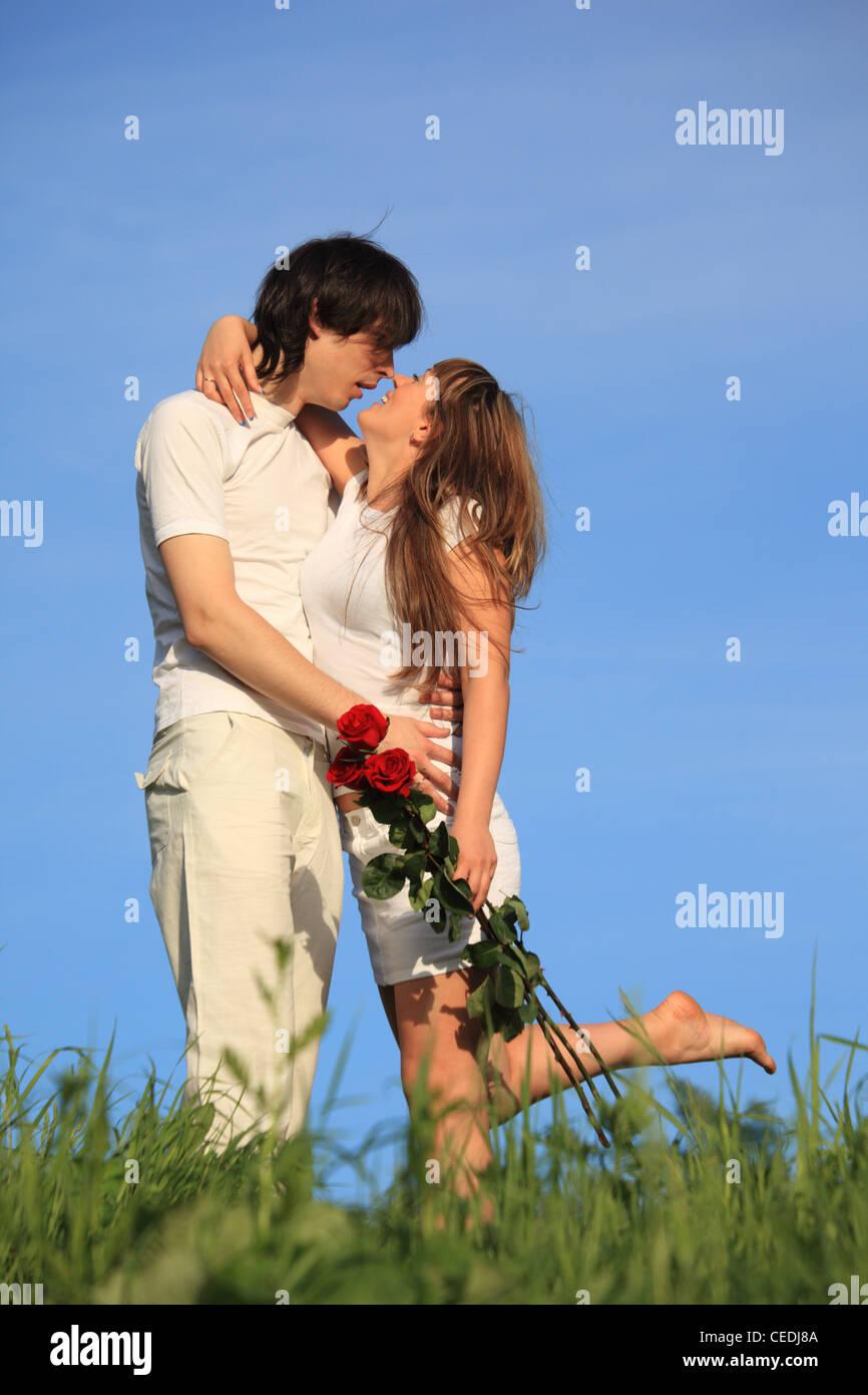 Ragazza con mazzo di rose baci guy su erba contro sky Immagini Stock