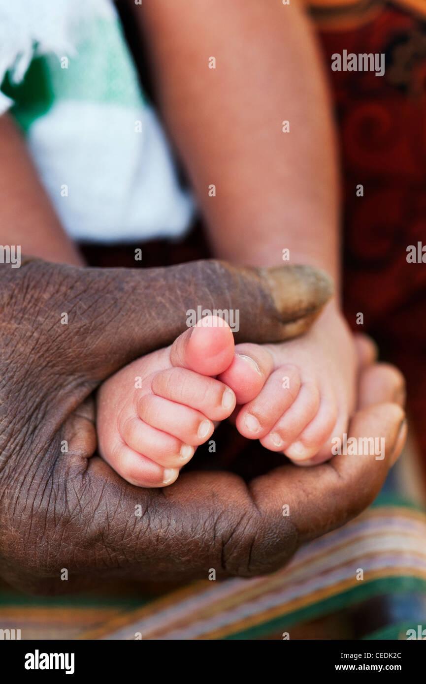 Nonna indiano holding neonati a piedi nudi. Andhra Pradesh, India.Il fuoco selettivo. Immagini Stock