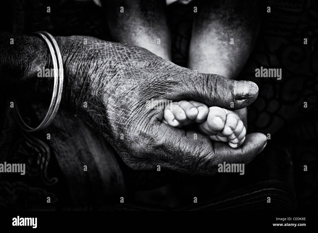Nonna indiano holding neonati a piedi nudi. Andhra Pradesh, India. Immagini Stock
