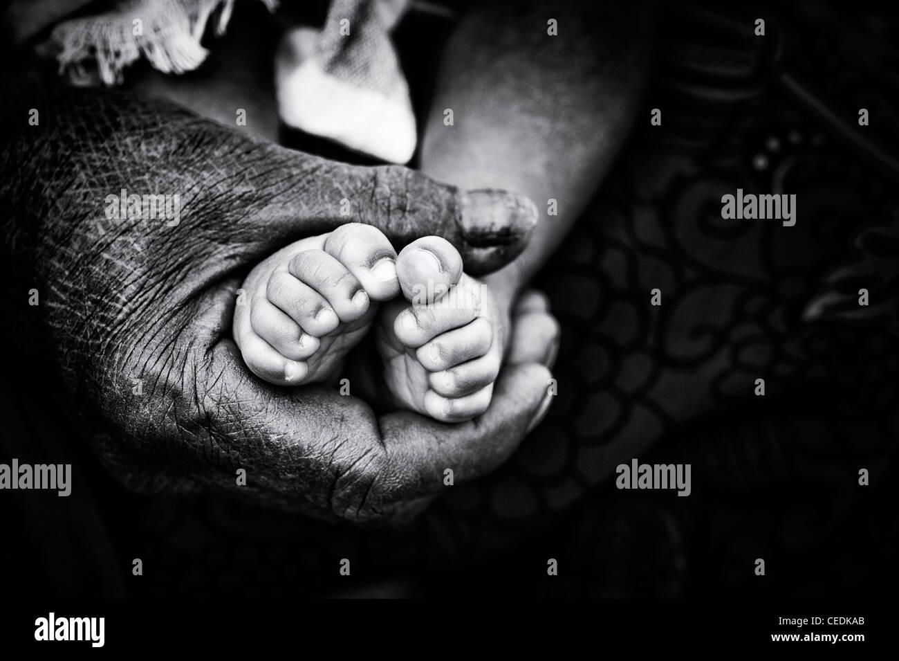Nonna indiano holding neonati a piedi nudi. Andhra Pradesh, India. Il fuoco selettivo in bianco e nero. Immagini Stock