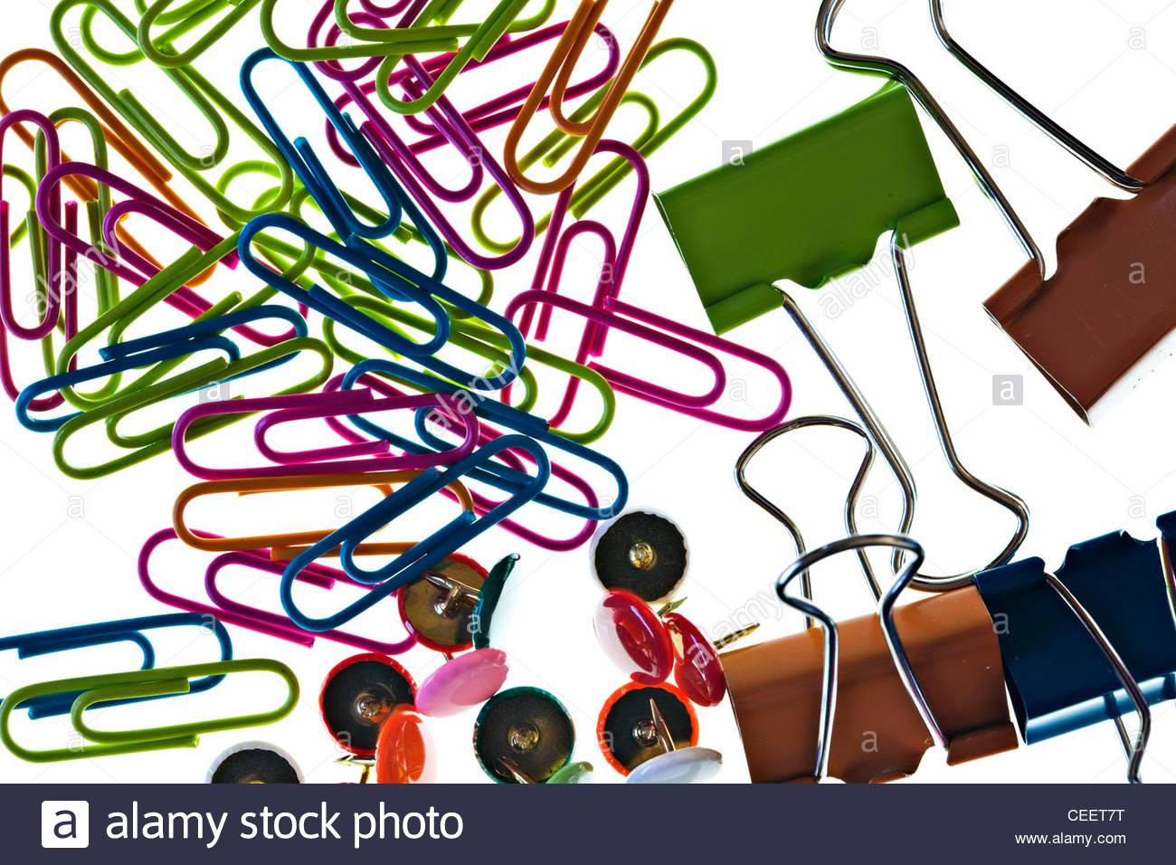 Close-up di carta colorata clip, puntine da disegno e bulldog clip su sfondo bianco Foto Stock