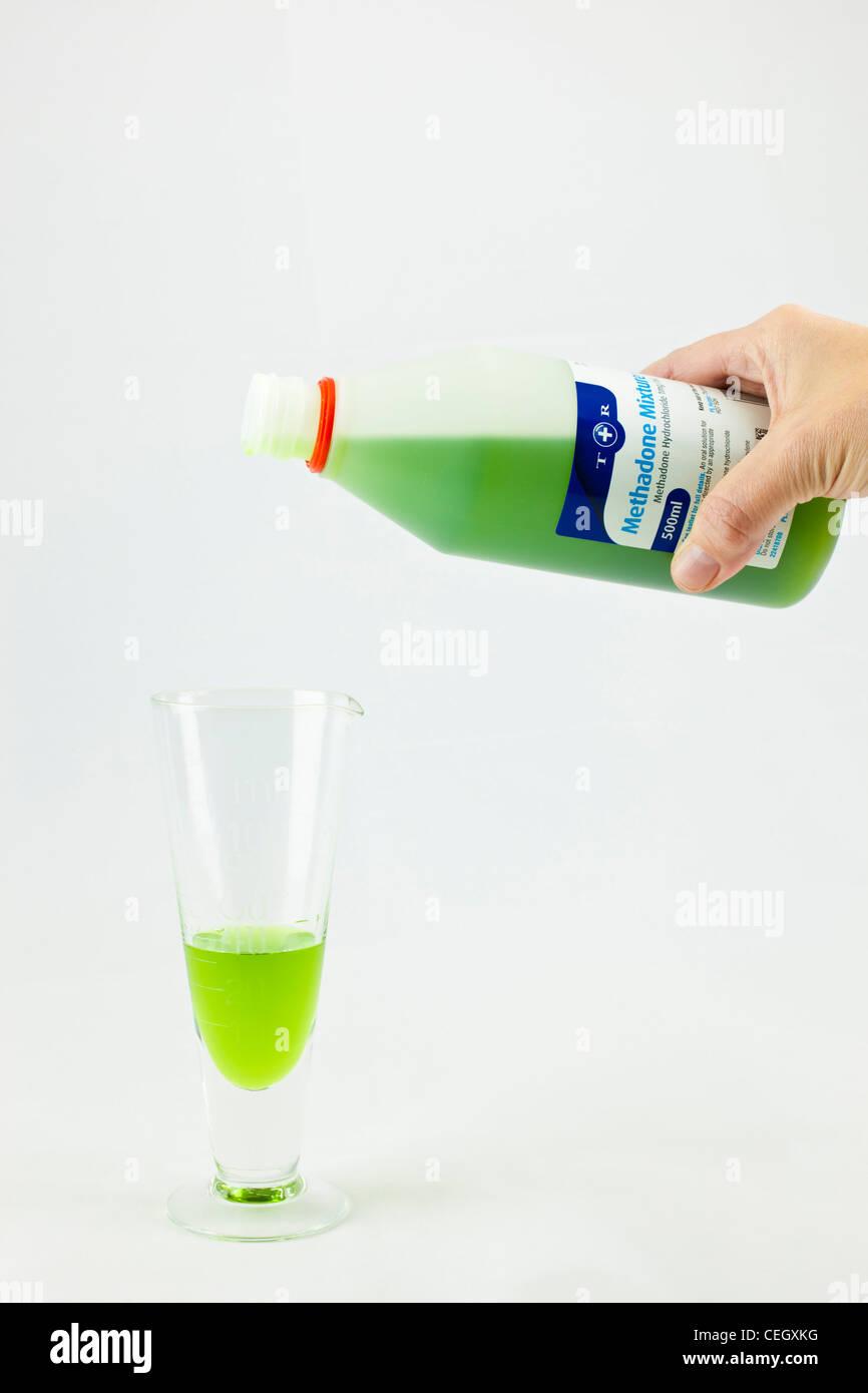 Il farmacista versando il metadone da una bottiglia di una misura graduata per dare una dose misurata di un tossicodipendente Immagini Stock