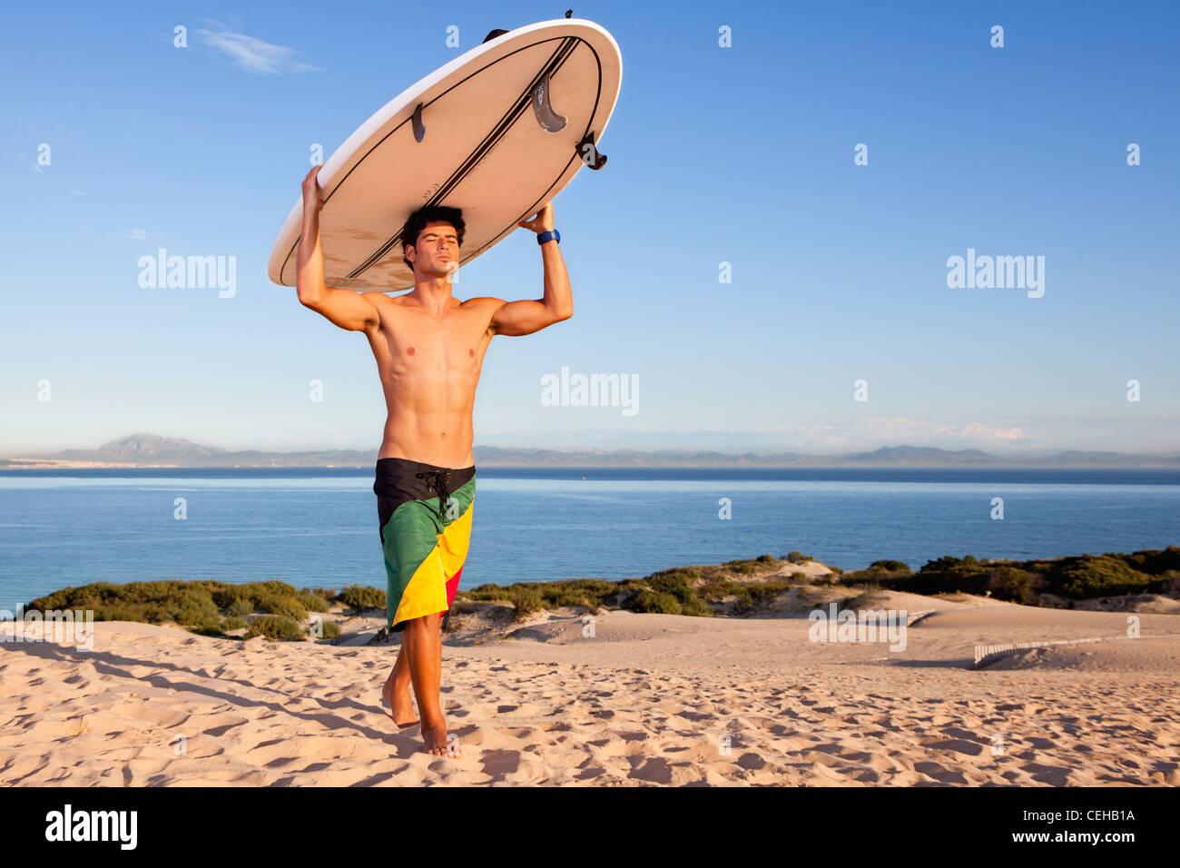 Surfer portando la sua scheda sopra la sua testa Immagini Stock