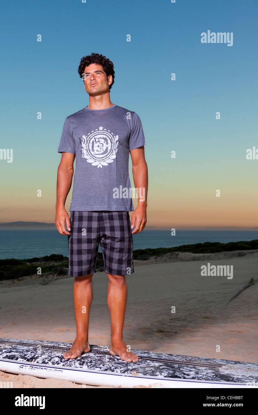 Giovane uomo in posa sulla spiaggia e la vostra tavola da surf Immagini Stock