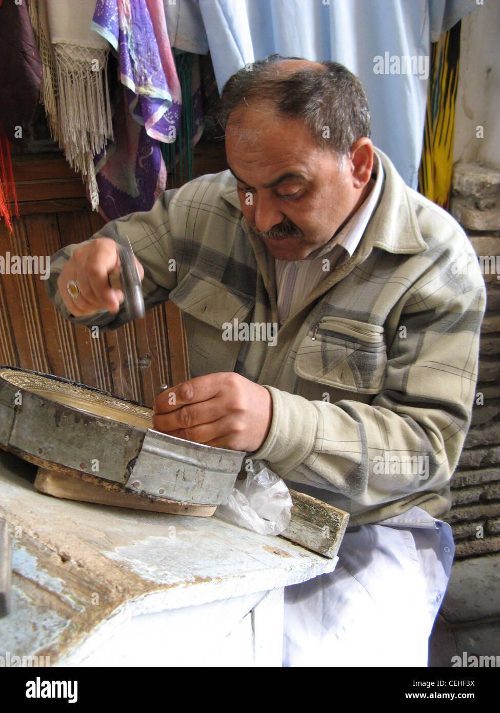 Uomo tradizionale in Uzbekistan rendendo un ornamento. Immagini Stock