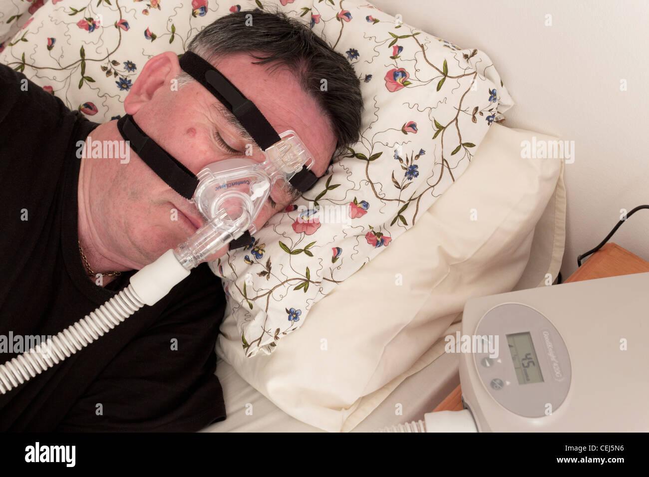 Uomo che utilizza un CPAP maschera facciale e la macchina utilizzata per il trattamento di apnea nel sonno. Immagini Stock