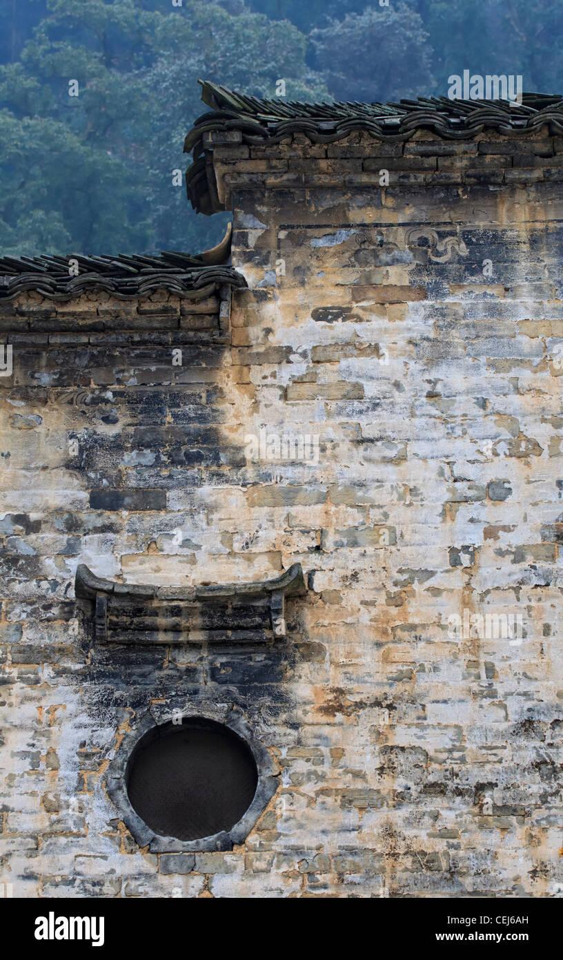 Un Cinese hui stile casa residenziale, alta bianco parete testurizzata e tetto nero con design a più livelli Foto Stock