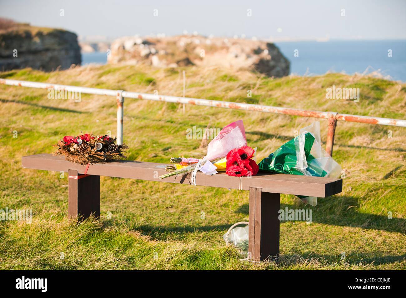 Fiori su un banco di memorial vicino Souter, tra Newcastle e Sunderland, UK. Immagini Stock