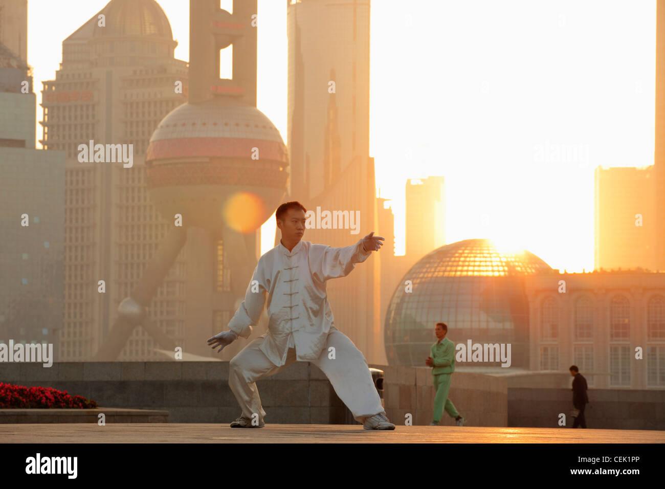 Uomo cinese facendo arti marziali al mattino sul Bund, Shanghai, Cina Immagini Stock