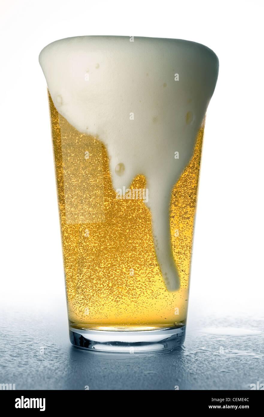 Bicchiere da birra traboccante Immagini Stock