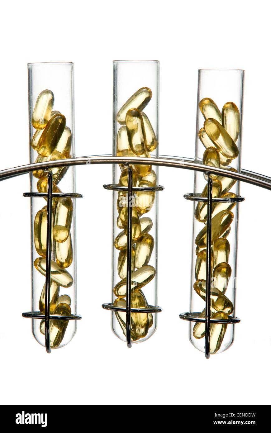 Generico liquido capsule riempite in provette in vetro in un piedistallo cromato Immagini Stock