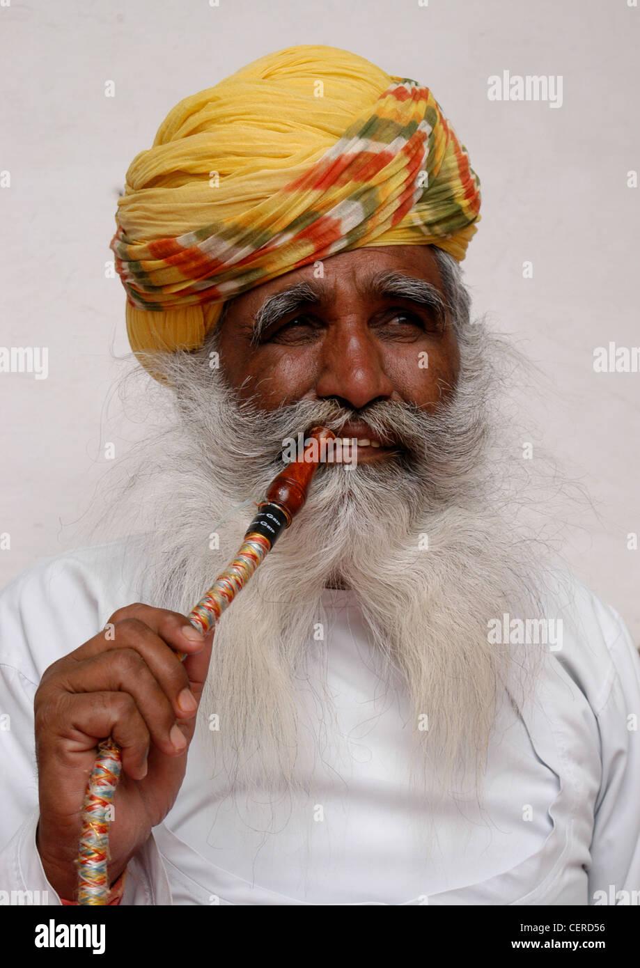 Rajput-uomo che rappresentano il Regno di Rajasthani che mostra il metodo di fumo filtrato il fumo di tabacco attraverso Immagini Stock