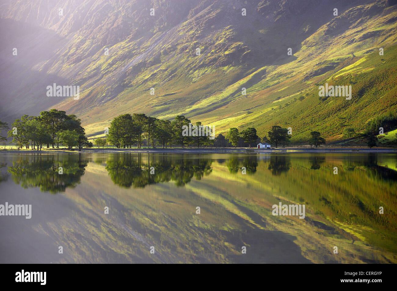 Riflessioni sulla riva del Buttermere all'alba, Cumbria, Distretto dei Laghi, Cumbria, England, Regno Unito Immagini Stock