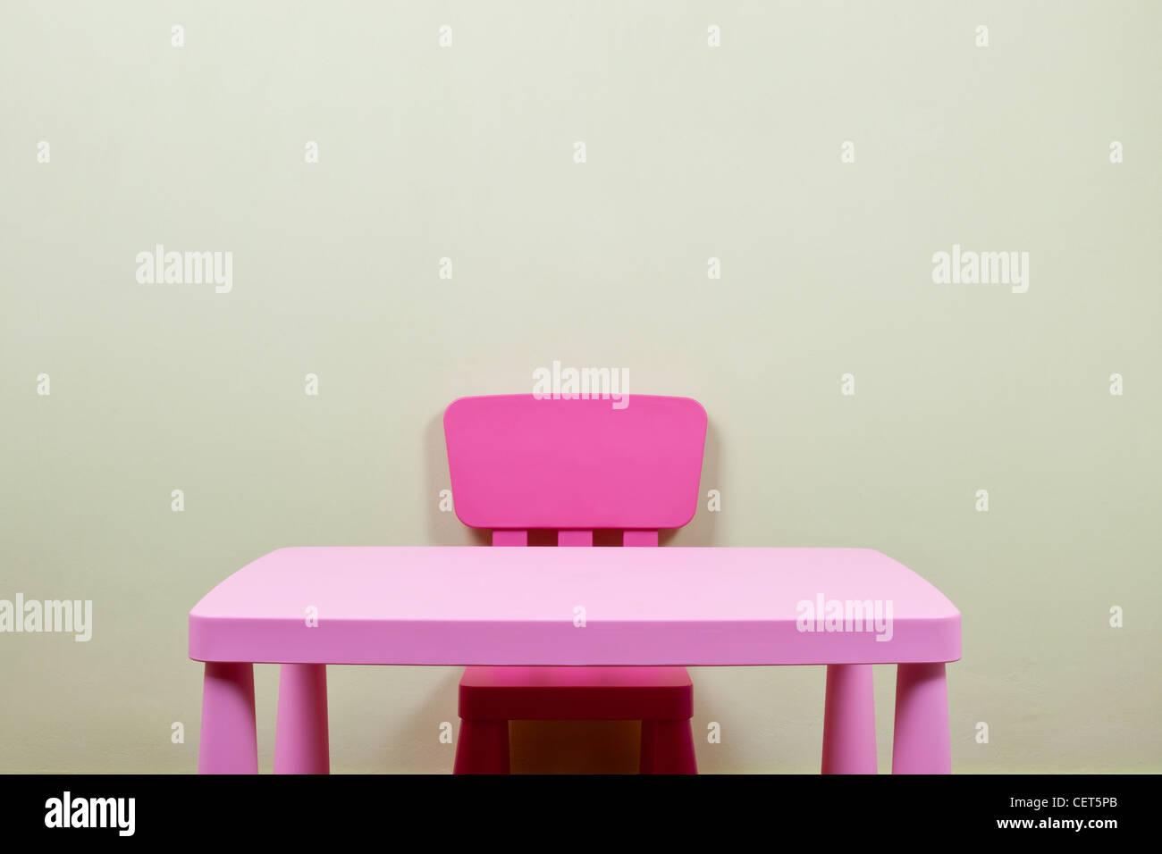 Colore rosa bambini scrivania e sedia contro un muro grezzo Immagini Stock