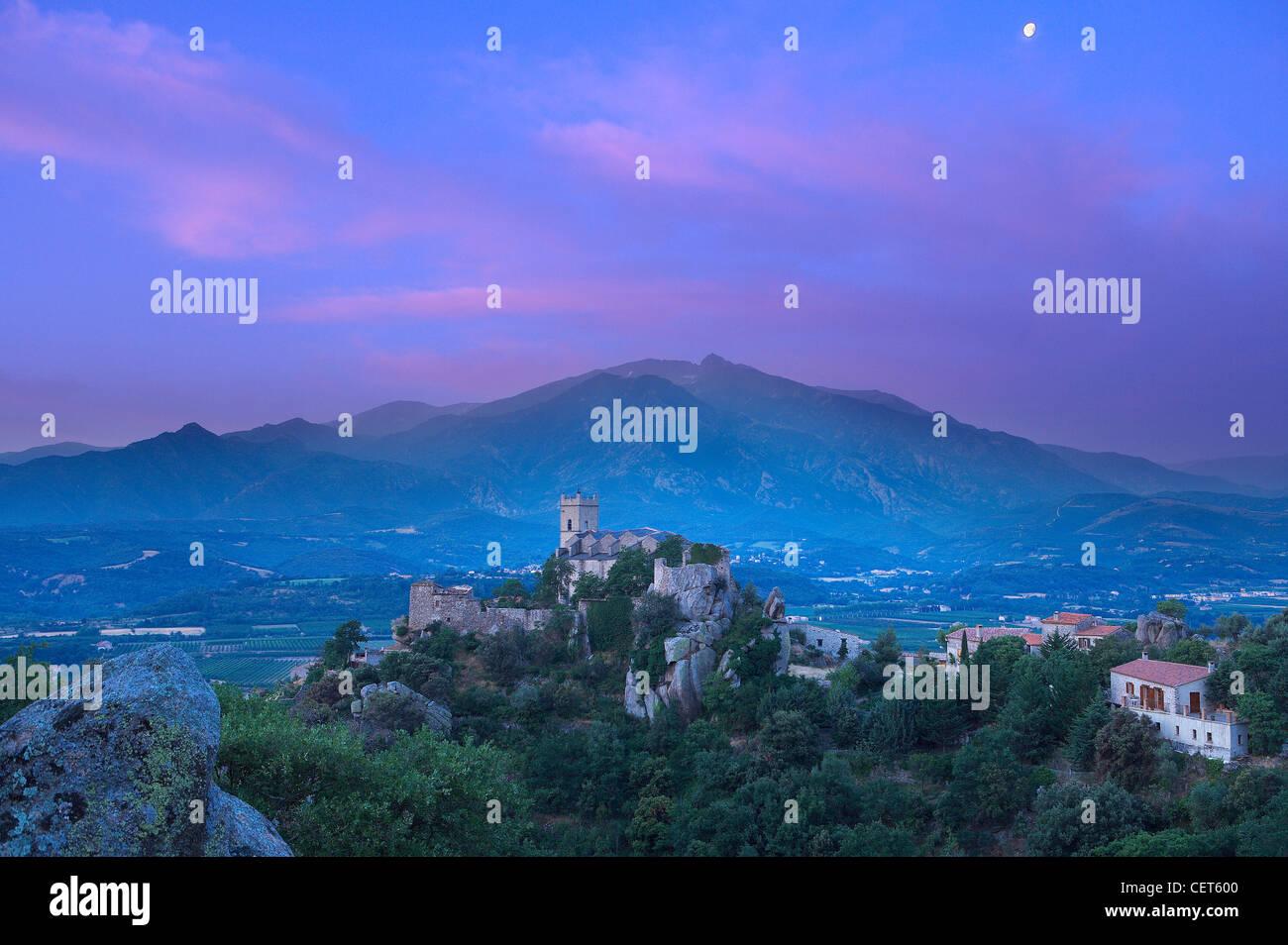 Il villaggio di Eus appollaiato sulla cima di una collina con il Pic de Canigou oltre i Pirenei, Languedoc-Rousillon, Immagini Stock