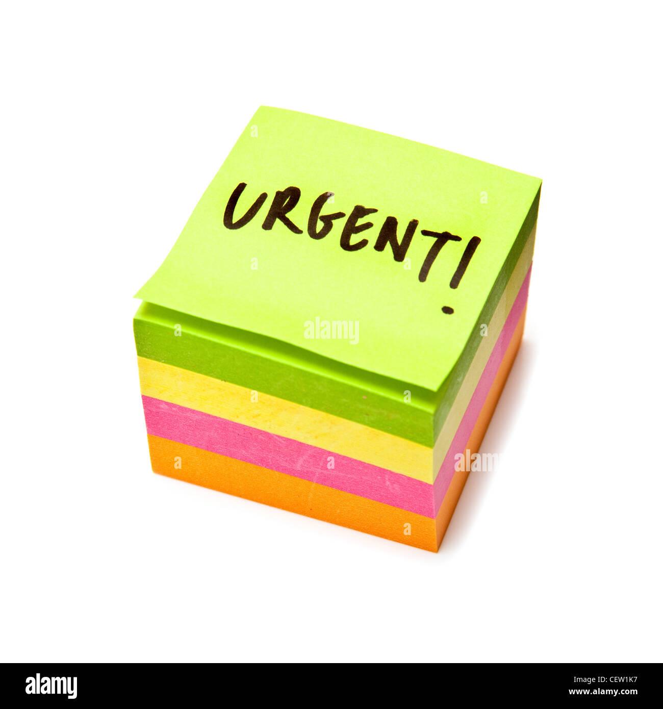 Nota adesiva pad con il messaggio urgente isolato di sfondo per studio. Immagini Stock