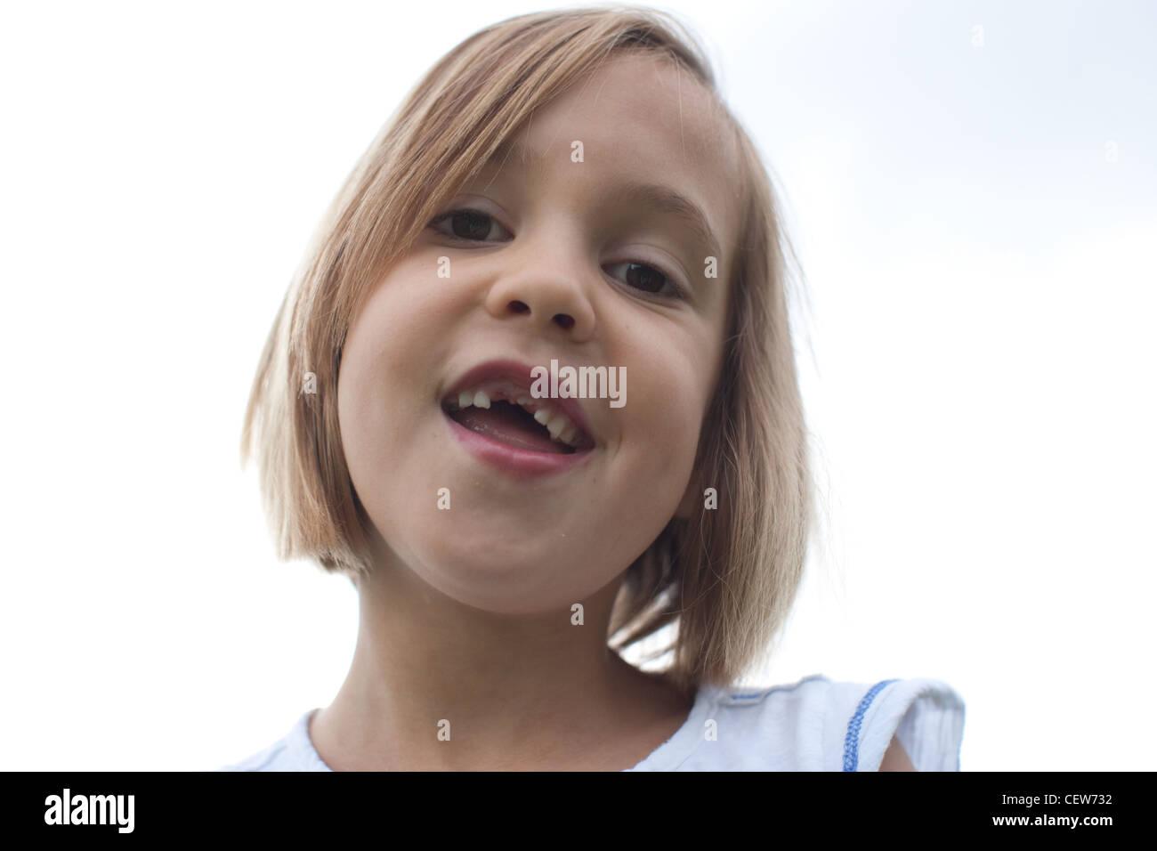 Sei anni di sorridere con grande gap e mancanti di denti frontali, sky in background. Foto Stock
