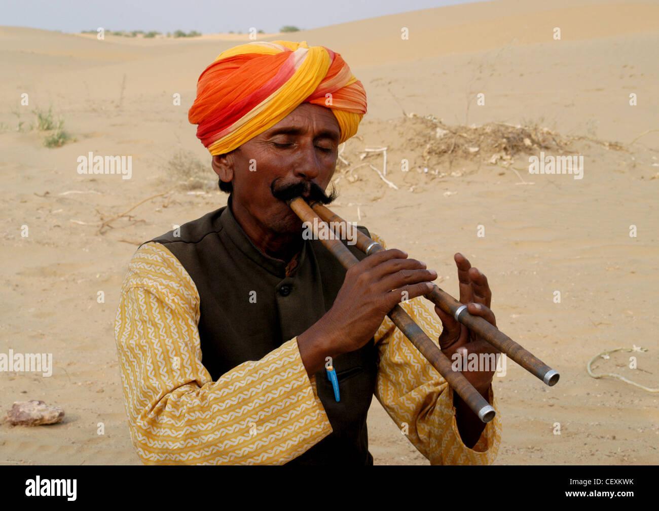 Rajput uomo con i baffi la riproduzione unica musica classica notevolmente con due flauti divertente turisti in Immagini Stock