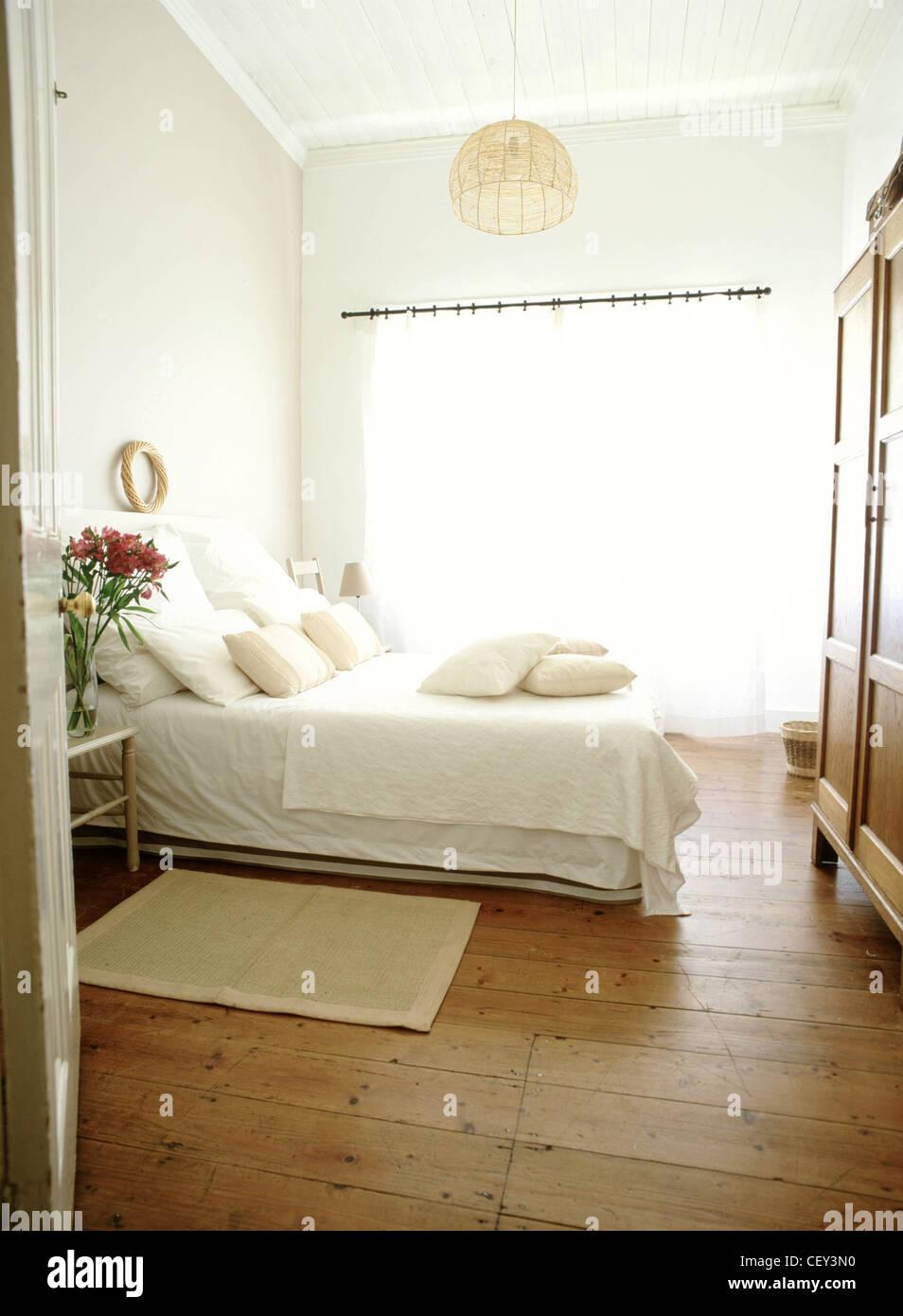 Camera da letto una parete rosa, tende bianche, basket ...