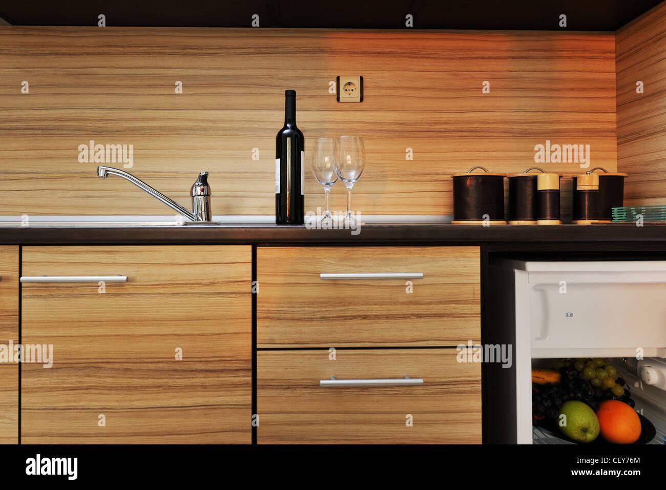Cucina moderna con mobili in legno con lavandino, frullatore e frigo Immagini Stock