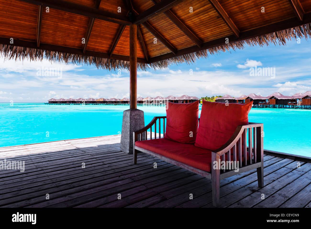 Divano Rosso Cuscini : Divano rosso withtwo cuscini sul molo in laguna tropicale foto