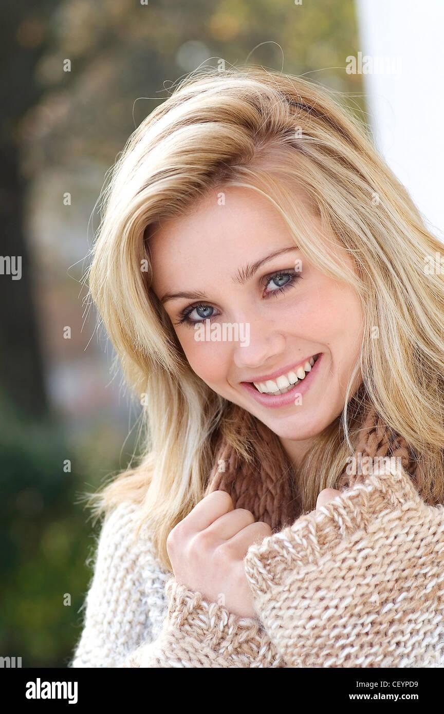 Femmina lunghi capelli biondi e gli occhi blu di indossare una maglia  allentati i fiocchi d avena ponticello colorato un rotolo su collo Lei sta  guardando ... b31b480fa99