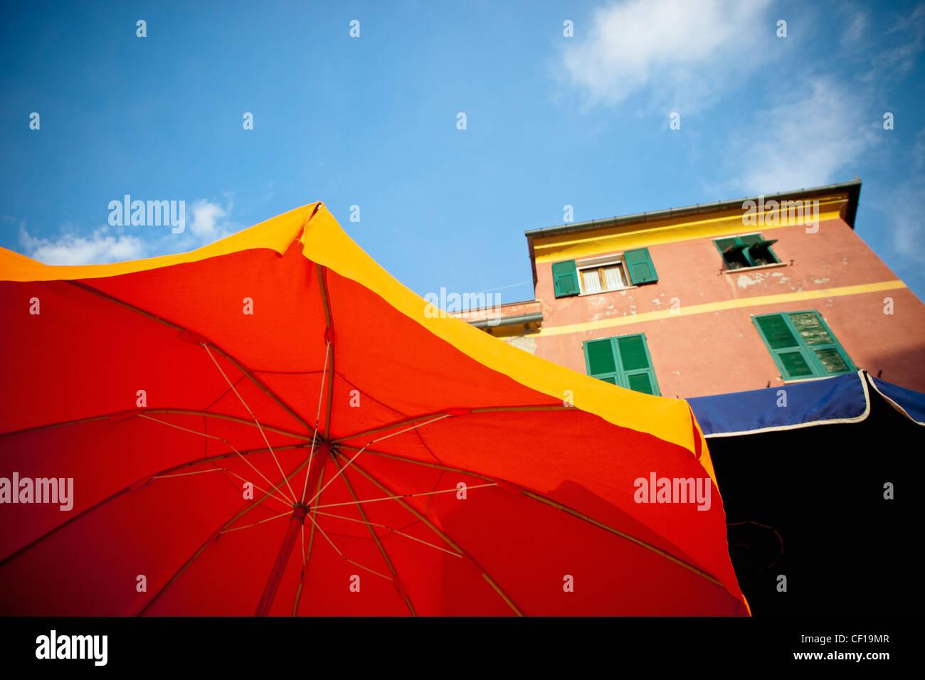 Il giallo e il Patio Bbue ombrelloni al di sotto di un edificio; Vernazza Liguria Italia Immagini Stock